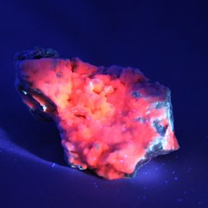 Fluorescent manganocalcite crystal cluster under UV light